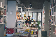 Beautiful young brunette posing in a bookstore Stock Photos