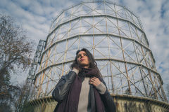 Beautiful young brunette posing in front of a gasometer Stock Images