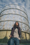 Beautiful young brunette posing in front of a gasometer Royalty Free Stock Image