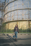 Beautiful young brunette posing in front of a gasometer Stock Photo