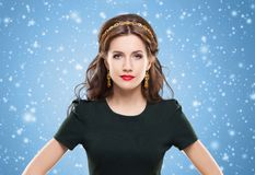 Beautiful, young brunette posing with golden headband and earrin. Beautiful brunette with luxury golden necklace over blue winter background. Christmas concept Stock Photos