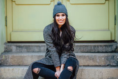Beautiful young brunette  posing and  sitting on a bench in the city streets Royalty Free Stock Image