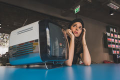 Beautiful young brunette posing beside a vintage tv Stock Photos