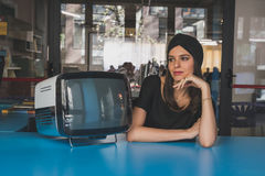 Beautiful young brunette posing beside a vintage tv Royalty Free Stock Photo