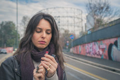 Beautiful young brunette putting on lipstick in the city streets Stock Images