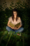 Beautiful young brunette reading a book. Stock Photo