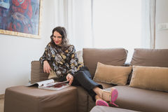 Beautiful young brunette reading on a couch Royalty Free Stock Images