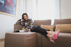 Beautiful young brunette reading on a couch Stock Images