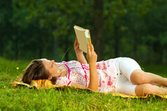 Beautiful young brunette reading on a meadow in the park Royalty Free Stock Photos