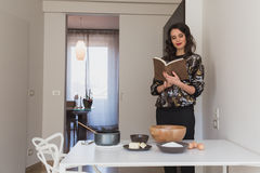 Beautiful young brunette reading recipe book Royalty Free Stock Photos