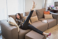 Beautiful young brunette relaxing on a couch Stock Image
