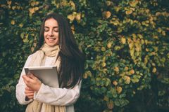 Beautiful young brunette sitting on a fallen autumn leaves in a park, reading an e-book on a tablet computer. Beautiful young brunette sitting on a fallen Stock Images