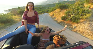 Beautiful young brunette sitting on hood of convertible car riding with friends stock footage