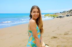 Beautiful young brunette in swimsuit kneeling on the beach.  stock photography