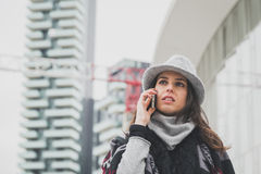 Beautiful young brunette talking on phone in the city streets Royalty Free Stock Images
