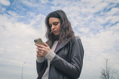 Beautiful young brunette texting in the city streets Stock Images