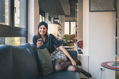 Beautiful young brunette texting on a couch Royalty Free Stock Images