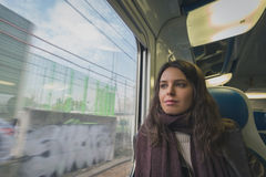 Beautiful young brunette travelling by train Stock Photo
