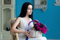 Beautiful young brunette in white dress and a pearl necklace sit. S in a chair with a bouquet of flowers in basket Royalty Free Stock Photos