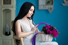 Beautiful young brunette in white dress and a pearl necklace sit. S in a chair with a bouquet of flowers in basket Stock Photos