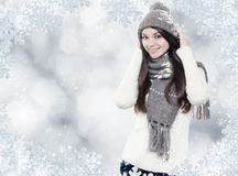 Beautiful young brunette with winter clothes. On silver background royalty free stock photos