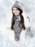 Beautiful young brunette with winter clothes. Beautiful young brunette with winter hat, scarf and gloves on winter background Royalty Free Stock Photography