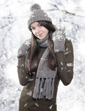 Beautiful young brunette with winter clothes. Beautiful young brunette with winter hat, scarf and gloves on winter background stock photography