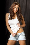 Beautiful young brunette woman. Posing in stretchy shirt and cut off jeans Stock Photo