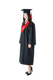 Beautiful young brunette woman in academic gown and mortarboard Royalty Free Stock Photos