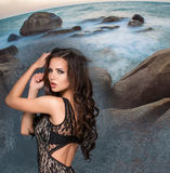 Beautiful young brunette woman against rocky shore or beach Stock Photos