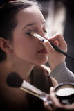 Beautiful young brunette woman applying powder with a brush Royalty Free Stock Photography