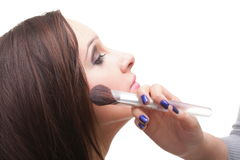 Beautiful young brunette woman applying powder with a brush Royalty Free Stock Image