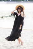 Beautiful young brunette woman in black dress, black sunglasses and straw hat walking on the sand on the beach and Stock Photo