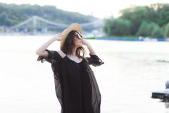 Beautiful young brunette woman in black dress, black sunglasses and straw hat walking on the sand on the beach and Stock Photos
