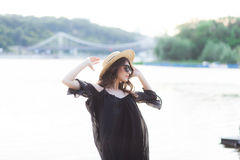 Beautiful young brunette woman in black dress, black sunglasses and straw hat walking on the sand on the beach and Royalty Free Stock Photo
