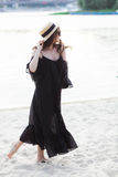 Beautiful young brunette woman in black dress, black sunglasses and straw hat walking on the sand on the beach and Stock Image