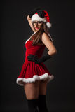 Beautiful young brunette woman with black retro glasses dressed as Santa Royalty Free Stock Photos