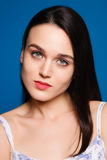 Beautiful young brunette woman on a blue background in the studio stock image