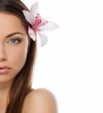 Beautiful young brunette woman. With blue eyes and orchid flower in her hair Royalty Free Stock Photography