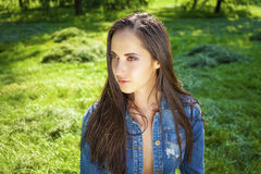 Beautiful young brunette woman in blue jeans jacket Stock Photography
