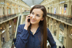 Beautiful young brunette woman calling by phone. In the shop Stock Photos