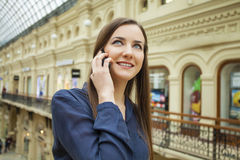 Beautiful young brunette woman calling by phone. In the shop Stock Image
