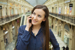 Beautiful young brunette woman calling by phone. In the shop Royalty Free Stock Image