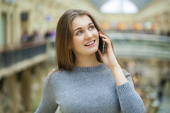 Beautiful young brunette woman calling by phone. In the shop Royalty Free Stock Images