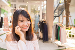 Beautiful young brunette woman calling by phone in shop. Beautiful young brunette woman calling by phone in the shop Stock Photography