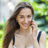 Beautiful young brunette woman calling by phone. Summer park outdoors Stock Image