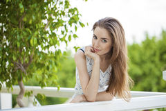 Beautiful young brunette woman calling by phone. Summer park outdoors Royalty Free Stock Photos