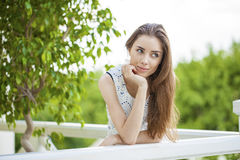 Beautiful young brunette woman calling by phone. Summer park outdoors Royalty Free Stock Images