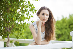 Beautiful young brunette woman calling by phone. Summer park outdoors Royalty Free Stock Photography