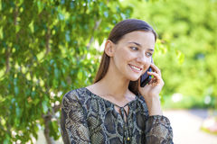 Beautiful young brunette woman calling by phone. Summer park outdoors Stock Photo